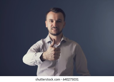 Handsome smiling guy showing thumbs up. Portrait of a handsome man on a dark background in the studio