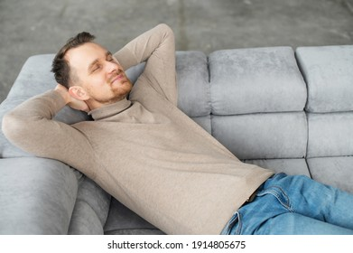 Handsome smiling guy take a nap lying on the comfortable sofa with eyes closed and hands behind head, attractive bearded man rests, daydreaming, resting