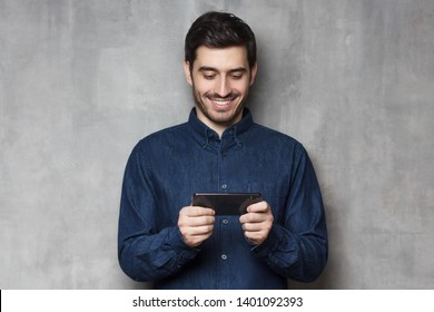 Handsome smiling guy using his smartphone for gaming or watching video isolated on gray textured wall background