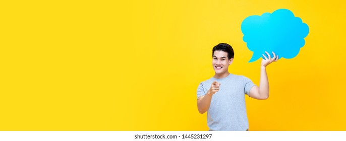 Handsome smiling happy Asian man holding speech bubble on yellow banner background with copy space