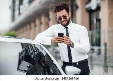 Handsome, smiling, happy, bearded businessman is using smartphone and standing near his car outdoors on the streets.
