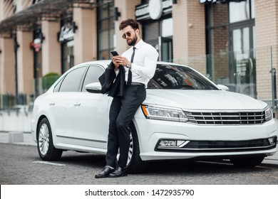 Handsome, smiling, happy, bearded manager is using smartphone and standing near his new white car on the street near the modern office center.