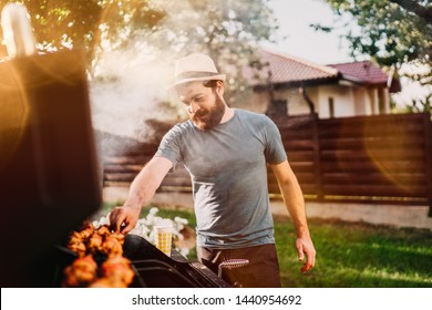 Handsome smiling, happy male preparing barbecue grill with meat and vegetables for friends