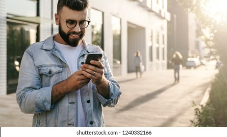 Handsome smiling hipster businessman with beard, in denim jacket and trendy glasses walks around city and using smartphone.Happy guy is standing outdoor and checking email on digital gadget.Lifestyle.