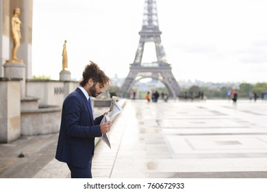 Handsome smiling journalist reading French public press close to Eiffel Tower. Attractive young man dressed in black suit, white shirt with blue tie. Cute guy has long fleecy hair and dark beard
