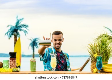 Handsome smiling Latin American bartender standing near the bar counter, preparing cocktail and adding something in the glass at the resort, toned image. Concept of preparation, relaxing and fun