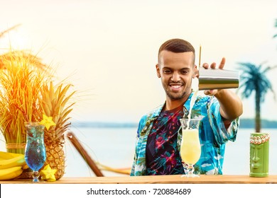 Handsome smiling Latin American bartender standing near the bar counter, preparing cocktail and adding something in the glass at the resort in rays of the sun. Concept of preparation, relaxing and fun