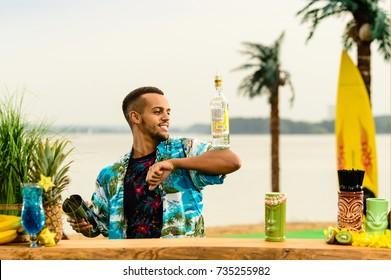 Handsome smiling Latin American bartender standing near the bar counter and holding a bottle of alcohol on the ocean. Concept of preparing cocktails, relaxing and resort