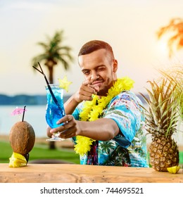 Handsome smiling Latin American bartender standing near the bar counter, holding a cocktail and winks on the ocean in rays of the sun. Concept of preparing cocktails, relaxing and resort