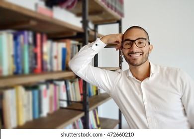 Handsome smiling Latino businessman with glasses leaning on a bookcase in library