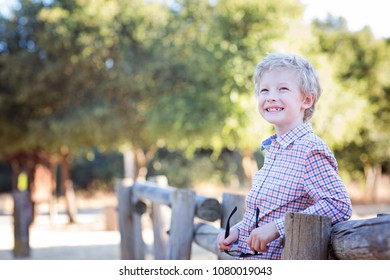 handsome smiling little boy in the park ready for school, back to school concept, copy space on left