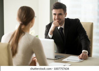 Handsome smiling male office worker in business suit sitting at desk with laptop in front of female colleague. Happy businessman talking with secretary. Positive first impression on job interview