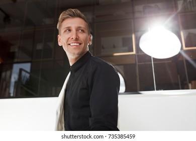 Handsome smiling man in black shirt looking away in backlit.