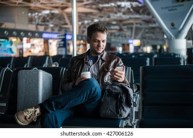 Handsome smiling man in casual wear holding luggage and messaging through his mobile phone while sitting at the hall of airport with coffee cup