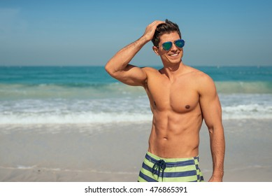 Handsome smiling man enjoying day on the beach.
