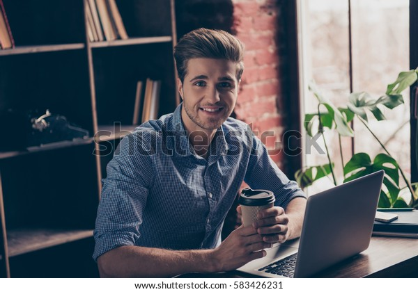 Handsome smiling man with laptop resting and drinking coffee