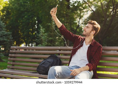 Handsome smiling man listening to music and taking selfie on the smartphone outdoors in the park, copy space
