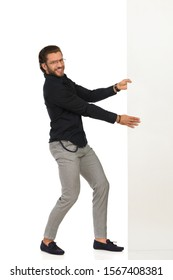 Handsome smiling man in moccasins, gray trusers, and black shirt is pulling big white banner. Side view. Full length studio shot isolated on white.