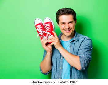 Handsome smiling man with red gumshoes on green background