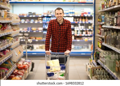 Handsome smiling man shopping in supermarket pushing trolley