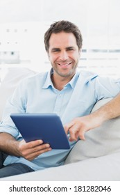 Handsome smiling man sitting on the sofa using his tablet pc at home in the living room