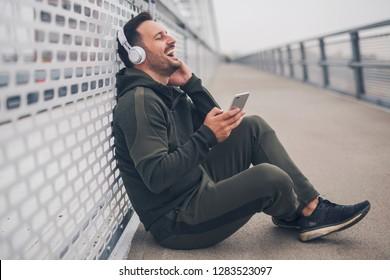 Handsome smiling man in sportswear sitting on the ground listening music on headphones enjoying.
