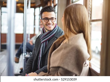 Handsome and smiling man talking whit his girlfriend on a vintage tram - Happy couple of lovers traveling - Concept about people, lovers and traveler
