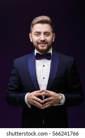 Handsome smiling man in tuxedo and bow tie looking at camera. Fashionable, festive clothing. emcee on dark background