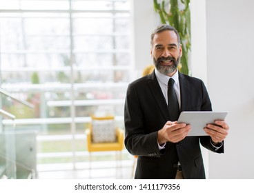 Handsome smiling mature businessman with digital tablet in the office working, reading or searching something