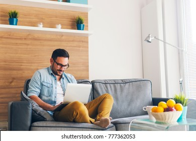 Handsome smiling modern man relaxing on couch and using laptop