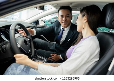 Handsome smiling salesman explaining interface of car to female customer