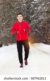 Handsome smiling sportsman in red sweater  jogging in the park and listening music. Outdoor activity.