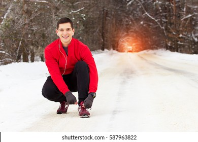 Handsome smiling sportsman in red sweater ties shoelaces of his sneakers. Outdoor activity.