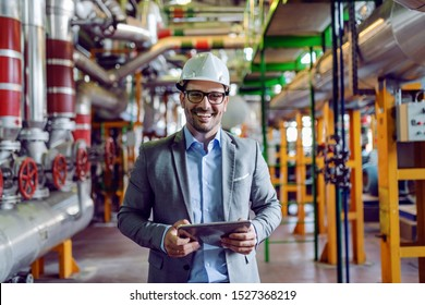 Handsome smiling supervisor in gray suit and with white helmet on head holding tablet while looking at camera. Power plant interior.