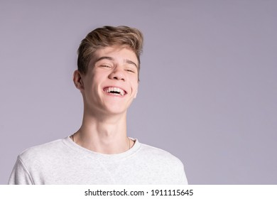 Handsome smiling teenager guy 16-18 years old over gray background. Close up emotional portrait of caucasian young man