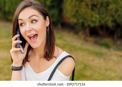Handsome smiling woman with mobile phone walking on the street