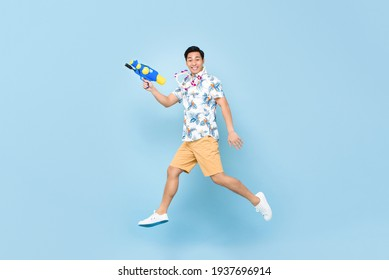 Handsome smiling young Asian man playing with water gun and jumping in studio blue background for Songkran festival in Thailand and southeast Asia