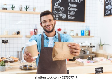 handsome smiling young barista holding coffee to go in paper cup and take away food in paper bag