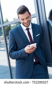 handsome smiling young businessman using smartphone outside