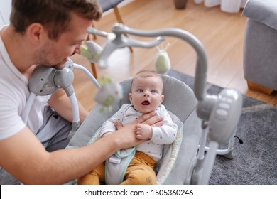 Handsome smiling young caucasian dad comforting his adorable 6 months old son. Baby sitting in baby rocker chair and looking amazed at toys.