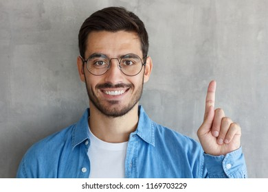 Handsome smiling young man in blue shirt adn round eyeglasses pointing up with his finger, isolated on gray textured wall