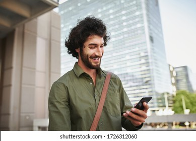 Handsome smiling young man in formal clothing using smartphone
