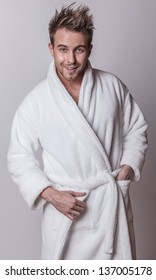 Handsome smiling young man in luxurious bathrobe.
