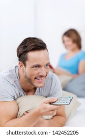 Handsome smiling young man relaxing on his bed with a remote control in his hand watching television