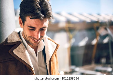 Handsome smiling young man standing at window in terminal of airport.