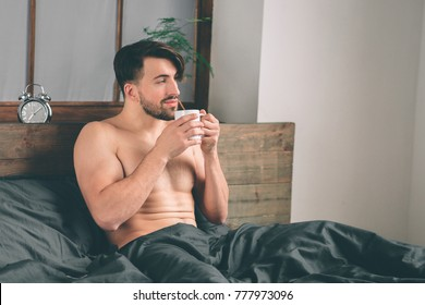 handsome smiling young naked man holding cup of coffee and looking away while sitting on bed