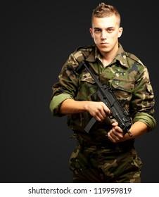 handsome soldier holding gun against a black background