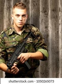 handsome soldier holding gun an old wooden background