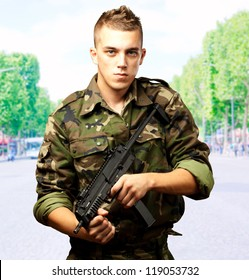 handsome soldier holding gun, outdoor