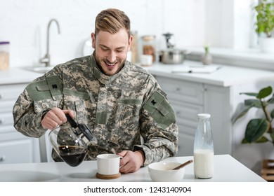Handsome soldier in uniform smiling and pouring coffee in cup at kitchen